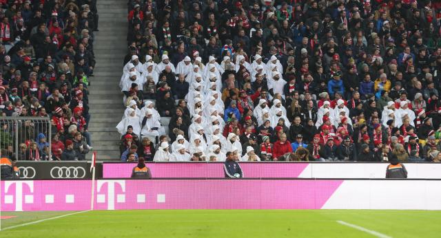 Spectators forming a white Telekom logo in the stands of the Allianz Arena.